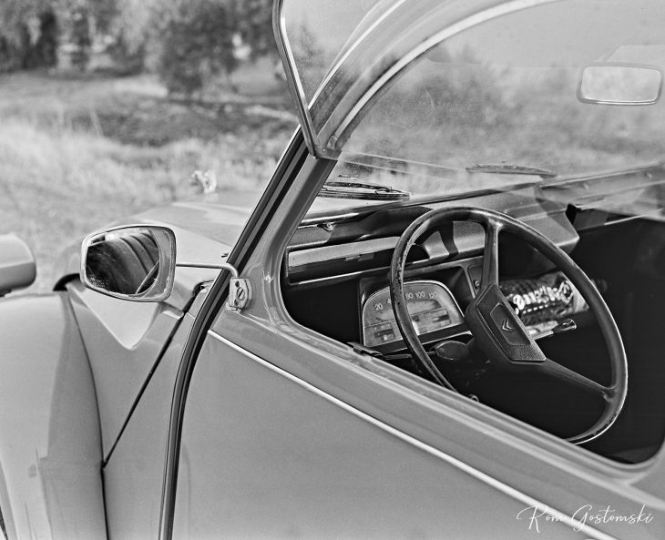 Looking in through the driver's door window at the steering wheel and front dash.