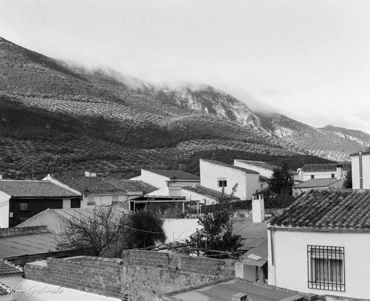 Black and white photo of village roofs. The photo was taken on an overcast day with low cloud obscuring the hills.